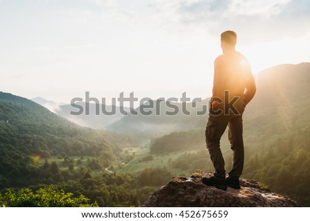 Traveler young man standing in the summer mountains at sunset and enjoying view of nature