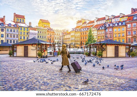 Traveler young woman walking with luggage on the Old Town Square with the Christmas market in Warsaw in the winter, Poland. #667172476