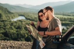 Travelers Couple on Road Trip, Man and Woman Using Map on Journey Near Their Car Over Beautiful Landscape