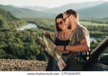 Travelers Couple on Road Trip, Man and Woman Using Map on Journey Near Their Car Over Beautiful Landscape Foto stock ©