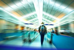 Travelers rushing through an airport terminal