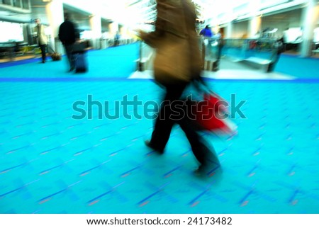 Travelers rushing through an airport terminal