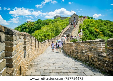 Travelers walking on the great wall of China, The construction of the wonders of the world on the mountain filled with green trees.