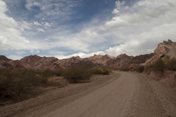 Traveling along the dirt road across death valley. The desert road, arid desert and rocky hills.