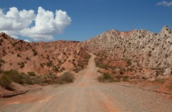 Traveling along the dirt road across the desert and red hills.