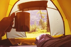 traveling and spending time in tent while drinking coffee in the morning. View from inside. Camper holding mug with hot tea inside the tent in the background of a beautiful mountain landscape.