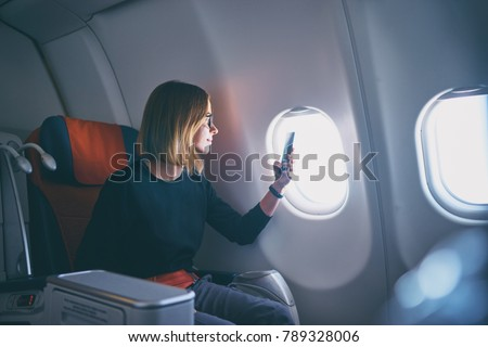 Traveling and technology. Flying at first class. Pretty young businees woman taking photo on smartphone while sitting in airplane.