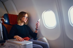 Traveling and technology. Flying at first class. Pretty young businees woman using smartphone while sitting in airplane.