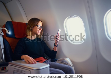 Traveling and technology. Flying at first class. Pretty young businees woman using smartphone while sitting in airplane. #1012511908