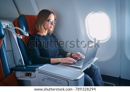 Traveling and technology. Flying at first class. Pretty young businees woman working on laptop computer while sitting in airplane.