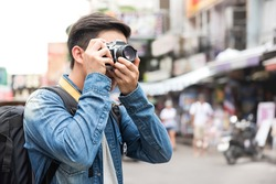 Traveling Asian male tourist backpackers taking photo in Khao san road,  Bangkok, Thailand on holidays