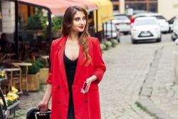 Traveling business woman wearing red cloak walks down city street.