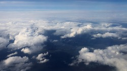 Traveling by air. View through an airplane window. Flying over the Mediterranean Sea through cirrus and cumulus clouds and little turbulence, showing Earth's atmosphere.