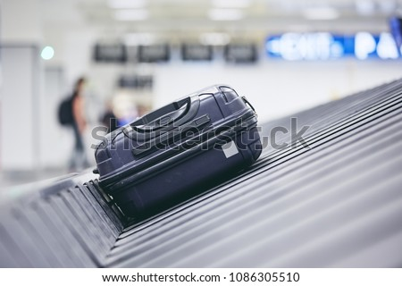 Traveling by airplane. Suitcase on baggage claim in airport terminal.