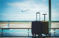 Traveling by airplane. Two suitcases in airport departure lounge, vacation concept or business travel, airplane taking off on the background, luggage in waiting area airport terminal