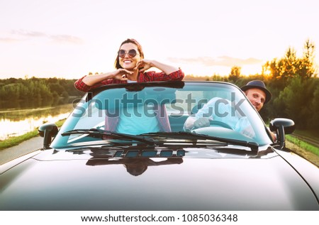 Traveling by car - couple in love go by cabriolet car in sunset time