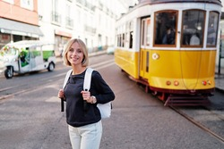 Traveling by Portugal. Happy young woman with rucksack walking by streets in Lisbon.
