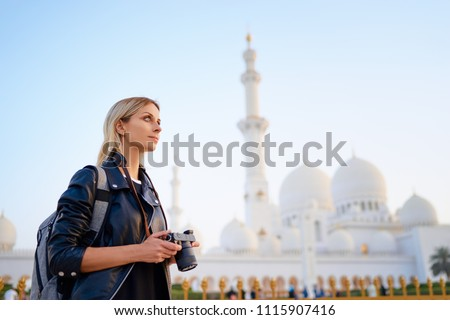 Traveling by Unated Arabic Emirates. Pretty Young Woman with camera standing near the Sheikh Zayed Grand Mosque, famous Abu Dhabi sightseeing.