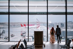 Traveling concept. Back view of man and woman standing near the window of international airport terminal.