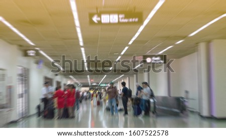 Traveling concept. Travelers asian walking with a luggage at airport terminal and airport terminal blurred crowd of Travelling people on the Background.