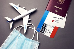 Traveling during COVID-19 pandemic, passport with airline ticket, covid-19 negative test, medical masks and plane on grey background, airport security health and safety check concept