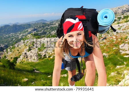 Traveling girl with backpack hiking in the mountains, freedom concept