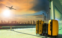 traveling luggage in airport terminal and passenger plane flying over sky