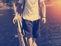 Traveling man walking across hanging bridge in good sunny day over the river (intentional sun glare and vintage color)