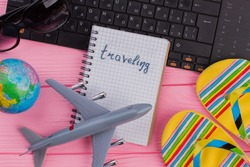 Traveling on notebook with woman's traveler accessories glasses wallet and flip-flops on pink table top background. Globe black keyboard grey small airplane.