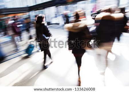 traveling people in motion blur at the railway station