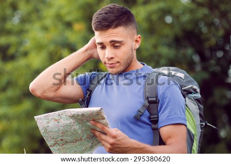 Traveling. Portrait of a young handsome tourist wearing blue t-short and backpack standing, feeling lost scratching head and looking at the map in his hand