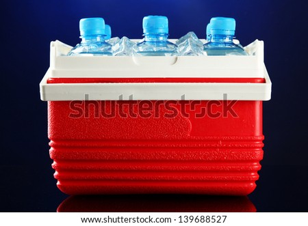 Traveling refrigerator with bottles of water and ice cubes, on blue background - stock photo