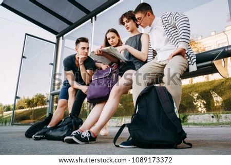Traveling, sightseeing, group travel, city tour, togetherness. Tourists sitting at bus stop planning their journey #1089173372