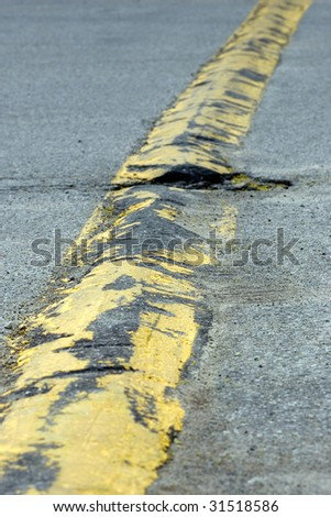 Traveling the length of a yellow speed bump, which has not been properly maintained.