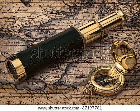 traveling theme: vintage telescope and compass at antique map