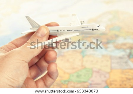 Traveling, tourism, communications and all things related - toy plane in hand with world map on background as a symbol of air transportation. Filtered image: cross processed vintage effect. #653340073