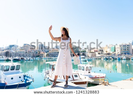 Traveling tourist woman on vacation in Heraklion Crete taking selfies at the port. Lovely elegant girl takes selfies visiting the famous Mediterranean Venetian port. Greek summer destination