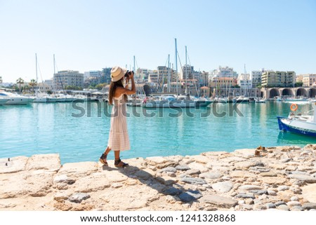 Traveling tourist woman on vacation in Heraklion Crete walking at the port. Lovely elegant girl in beige dress visiting the famous Mediterranean Venetian port. Greek summer destination #1241328868