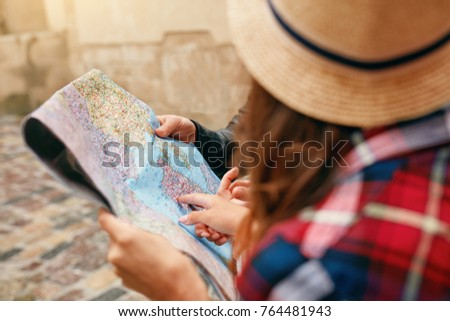 Traveling Using Map. Female Holding Map In Hands. Close Up Of Couple Of Tourists Looking For Destination Location On Paper City Map, Pointing At Places. View Of Hands. High Quality Image.
