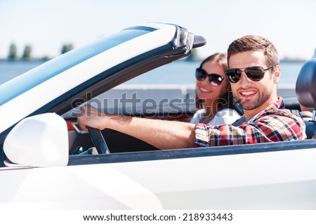 Traveling with comfort. Happy young couple enjoying road trip in their white convertible while both looking at camera and smiling #218933443
