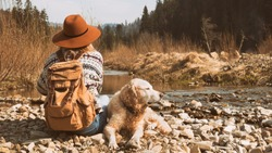 Traveling woman and wet golden retriever dog in nature. Stylish hipster in brown hat and wool sweater with vintage textile backpack near mountains river and forest.  Travel and wanderlust concept.
