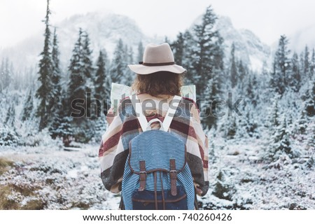 Traveling woman standing in the wild with map in front of amazing view. Wearing hat, poncho and backpack. Winter is coming, first snowfall. Wanderlust and boho style #740260426