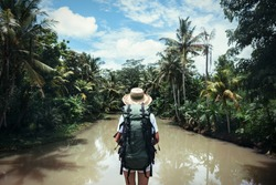 Traveling woman with backpack and straw hat looking at tropical river at sunny day