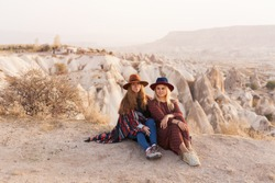 Traveling women wearing authentic boho chic style poncho, sweeter and hats smiling and have a fun  in Cappadocia valley, Turkey. Travel and wanderlust concept. Copy space background.