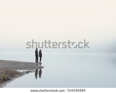 traveller couple standing on the lake shore and looking at the lake in rainy and foggy weather reflections on the lake