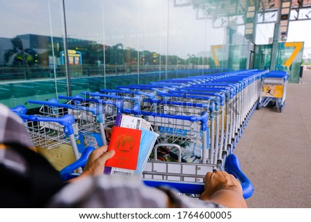 Traveller holding passport, mask, boarding pass, map, with hand on luggage trolley in airport; removing trolley from a row of parked trolleys. Travel essential concept; reopening. Selective focus.