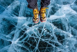Traveller man foot standing on cracks surface of the natural ice in frozen water at Olkhon Island, Baikal lake, Russia