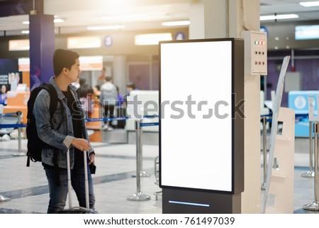 traveller man looking blank advertising billboard at airport. #761497039