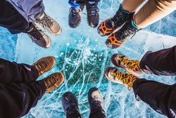 Traveller people foot standing on cracks surface of the natural ice in frozen water at Olkhon Island, Baikal lake, Russia
