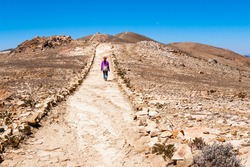 Traveller walking on a trail towards the horizon in Lake Titicaca